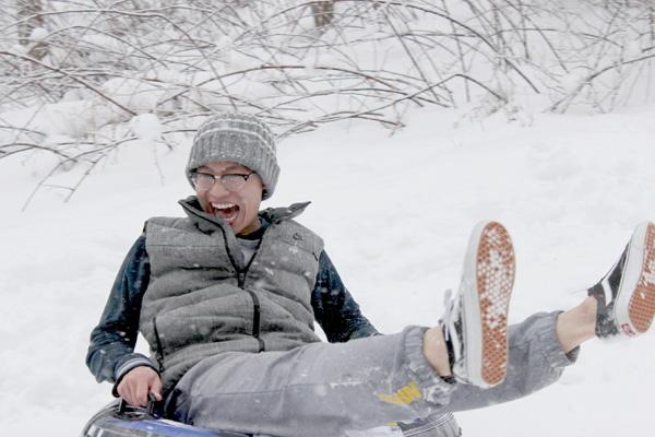 Students sled near log cabin