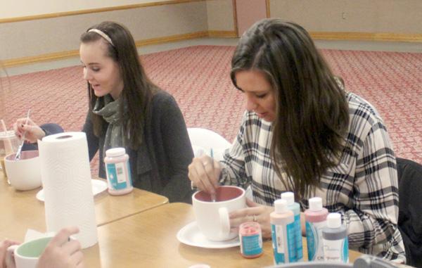 Fine Arts Club members help students paint mugs