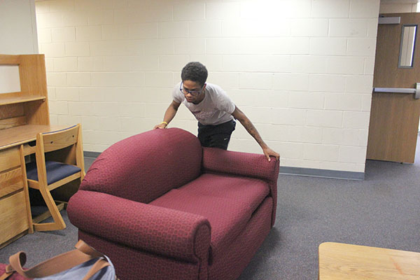 Sophomore TJ Mitchell-Scott moves furniture in Foxfire Lodge.