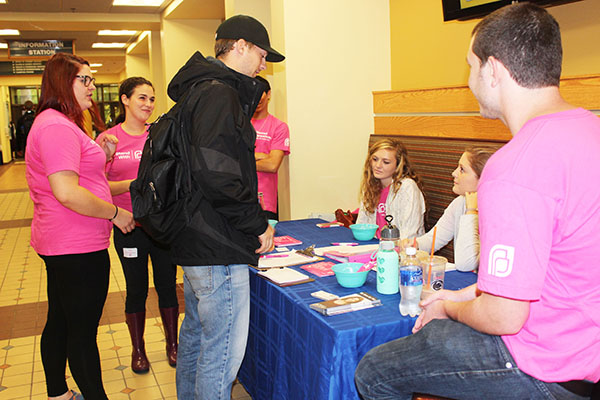 Travis Clark considers signing a petition to support Planned Parenthood. Club members from left to right, Kelsy Schorr, Tori Shriver and Jessie Savidge suround information table.