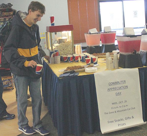 Sophomore Michael Mastovich grabs a cup of popcorn inside the Zone arcade in the Student Union during Commuter Appreciation Day last Wednesday.