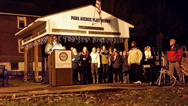 President Jem Spectar speaks to the crowd at the Light-Up event Tuesday, while the Pitt-Johnstown concert choir stands behind him waiting to sing their Christmas carols for the community.