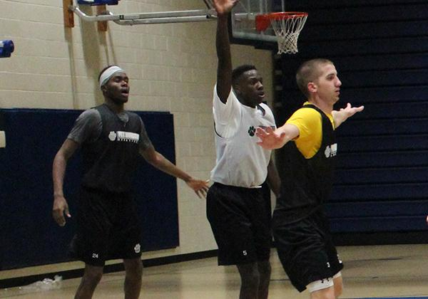 Freshman guard Olando King Jr. (center) attempts to avoid defenders senior guard Nate Snodgrass (right) and sophomore forward Levi Masua (left) during practice last week.