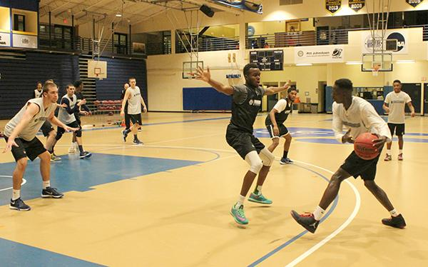 Sophomore forward Levi Masua (right center) plays defense on freshman teammate Olando King Jr. (far right) last week at practice in the Sports Center.