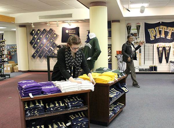 University bookstore staff member Aimee Weaber (left)  arranges apparel merchandise as co-worker Lyesha Waley walks by.