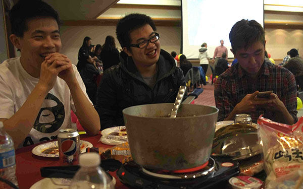 Chinese students Chen Yang, Zhu Zhuoming and Lu Zheping (left to right) are at a dining table Feb 9. at the Chinese New Year celebration in the Cambria Room.