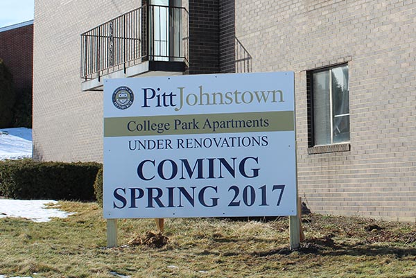 A newly placed sign in front of the College Park Apartments indicates upcoming renovation.