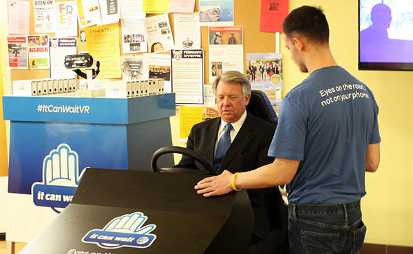 AT&T Employee Zack Smith (right) tells Sen. John Wozniak (left)  how the texting and driving simulator works.