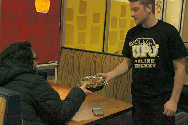Sodexo employee Eric Brimmeier (right) delivers food to Jewlee Romani at Mountain Cat Club on Feb. 4.