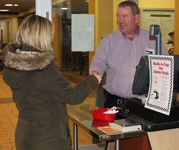 Sodexo General Manager Kevin Dicey (right) works the register in the Tuck Shop as senior Liz Lischick makes a purchase.