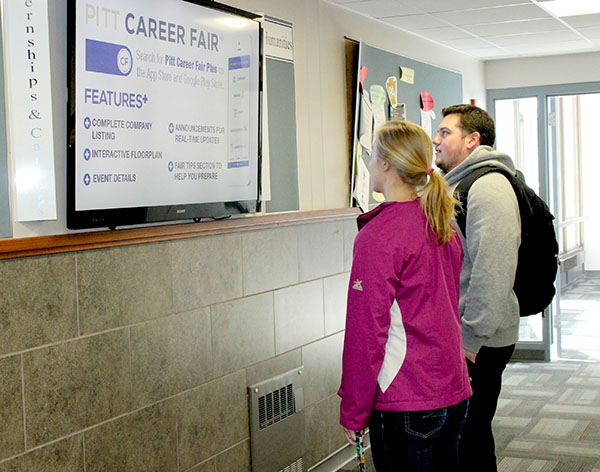 Freshman Alaina Thomas (left) and junior Gino Szegedy (right) read internship and career information displayed on the televsion located in Biddle Hall.