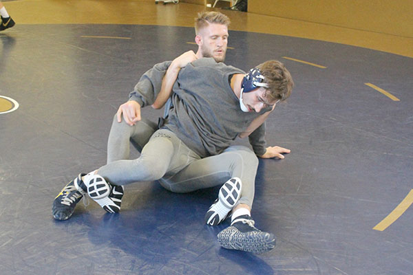 Sophomore Cody Law and redshirt sophomore Tyler Reinhart prep for nationals in the wrestling room last week at practice.