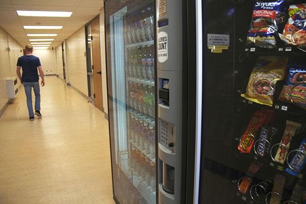 Freshman Nolan Pritts walks past a vending machine.