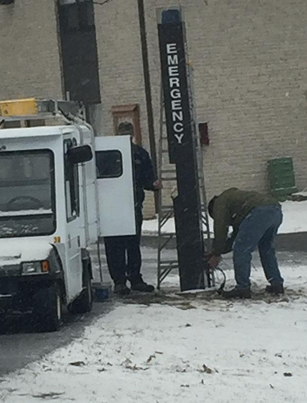Two maintenance employees work around an emergency phone in between Summit and Highland Townhouses.