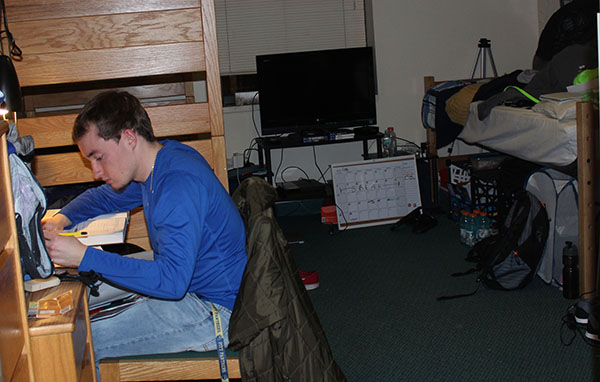 Sophomore Michael Leach studies at his desk in his Living/Learning Center dorm room. Leach lives with two roommates.