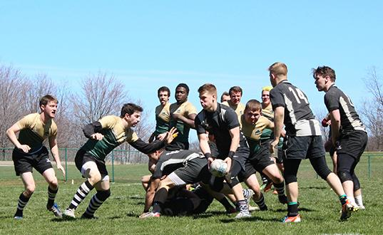 Surrounded by Point Park University rugby players are, Pitt-Johnstown's outside center sophomore Jake Bowser runs with the ball while teammates scrum half sophomore Grady Zagorac #14 and hooker sophomore Kiel Rutters look to block for him.