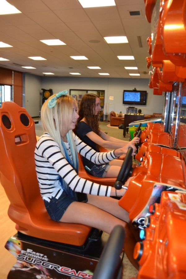 Juniors Danielle Majetic (left) and Savannah Johns (right) race against each other on the Fast and Furious racing consoles in the Zone.
