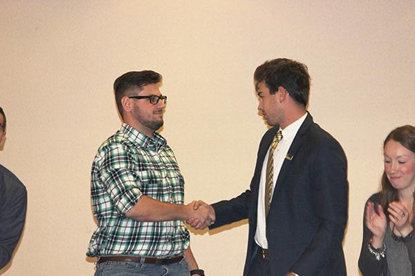 Senior Nick DiGiorgio (left) shakes Student Government Association President Kyle Maguire's hand after stepping down as vice president.