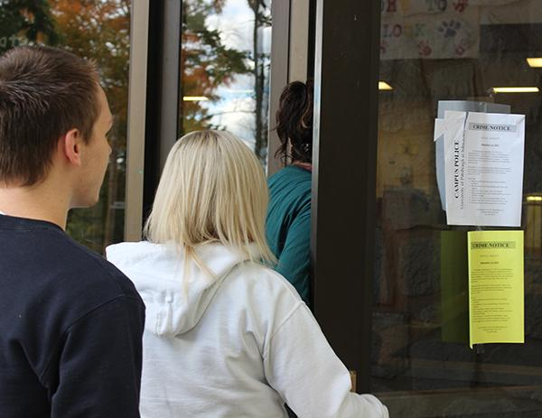 Freshmen Tyler Brown (left), Casey Atwell (middle) and Bri Fox enter Hemlock Hall where two crime notices are posted on the front door.