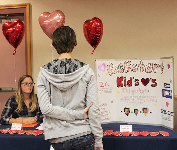 Freshman Rachel A. Heming stands in front of a Kickstart Kids' Hearts display at an Oct 12 activities fair in Cambria Room. The club's co-president Taylor Sultzbaugh attended the fair behind the display.