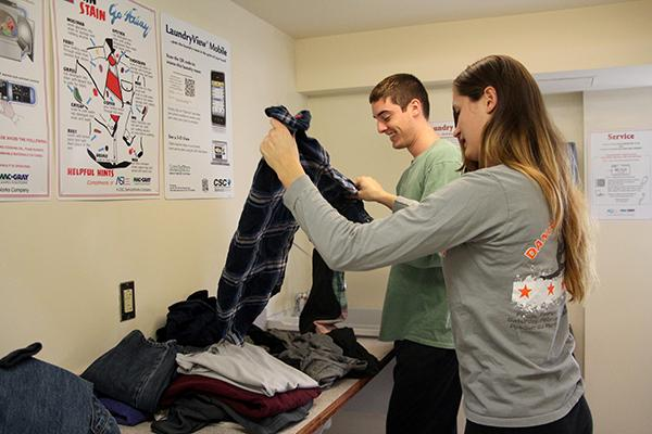 Seniors Drew Berkhoudt and Meagan Ruefle fold clothes after being notified that their laundry was done.
