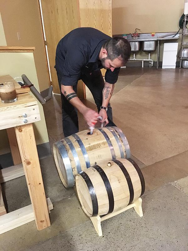Jordan Gwinn, Disobedient Spirits Distillery operations director, transfers bourbon from a barrel to a bottle in a distillery room.