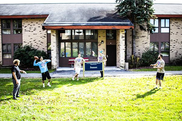 Kappa Delta Rho brothers play catch with a football in front of their lodge.