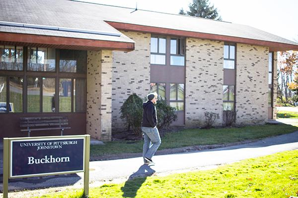 Senior Alex Taylor walks past Buckhorn Lodge, which is set to be renovated over the summer.