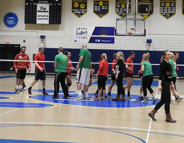 Participants of the students vs. staff volleyball game shake hands after the students defeated the staff 2-1.