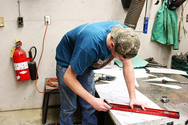 Senior Randy Moore works Thursday evening in a garage connected to the Physical Plant building.