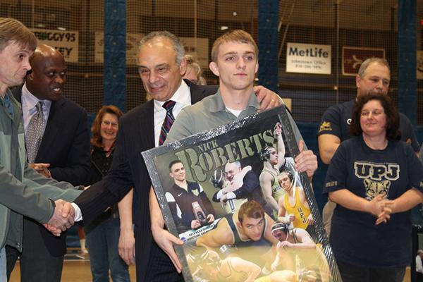 Senior wrestler Nick Roberts is congratulated as wrestlers were honered for their accomplishments Feb. 7 .
