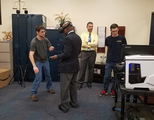 Senior Thomas Plutt helps President Jem Spectar with the new virtual-reality equiptment to be set up in the Zone. Sophomore Nick Marconi (right) and Student Affairs Vice President Shawn Brooks (second from right) monitor Spectar's experience on a computer.