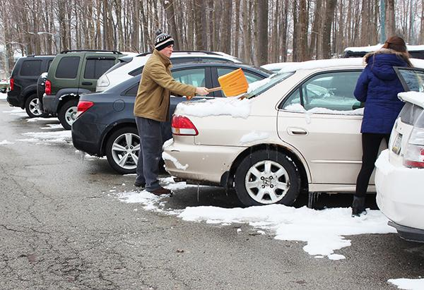 Junior Bradley Springer and non-student Heather Walker clean off a car at the North lodges' parking lot.