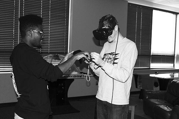 Senior Demar Watson helps freshman Allen Griffith learn how to use a virtual reality equipment in the Zone
