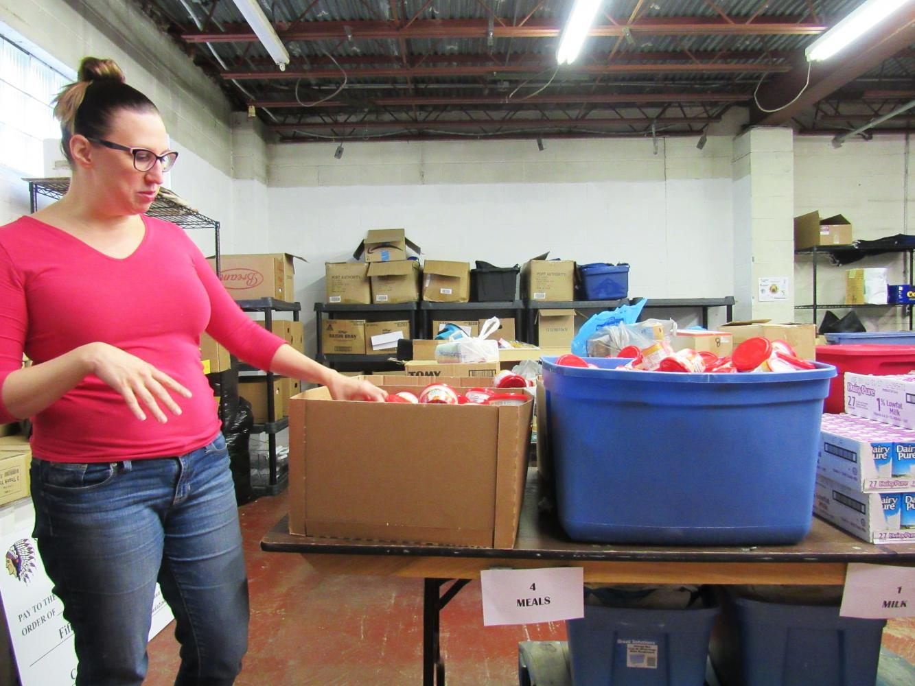 Natalie Kauffman, who coordinates the Cambria County Backpack Project, explains the assembly line that volunteers use to pack the backpacks each Monday night.