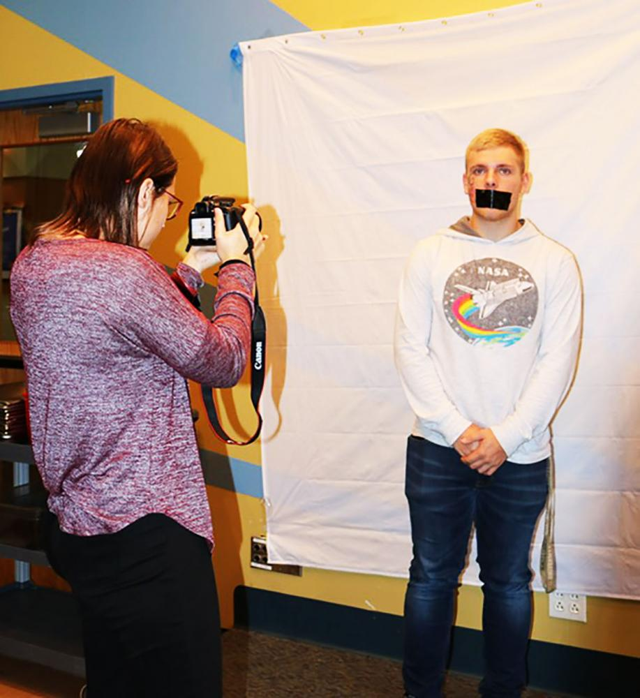 Sophomore Kayla Johnson takes a photograph of freshman Ben Nogroski at the Mt. Cat Club for a No Hate Photo Shoot sponsored by Alliance Club members.