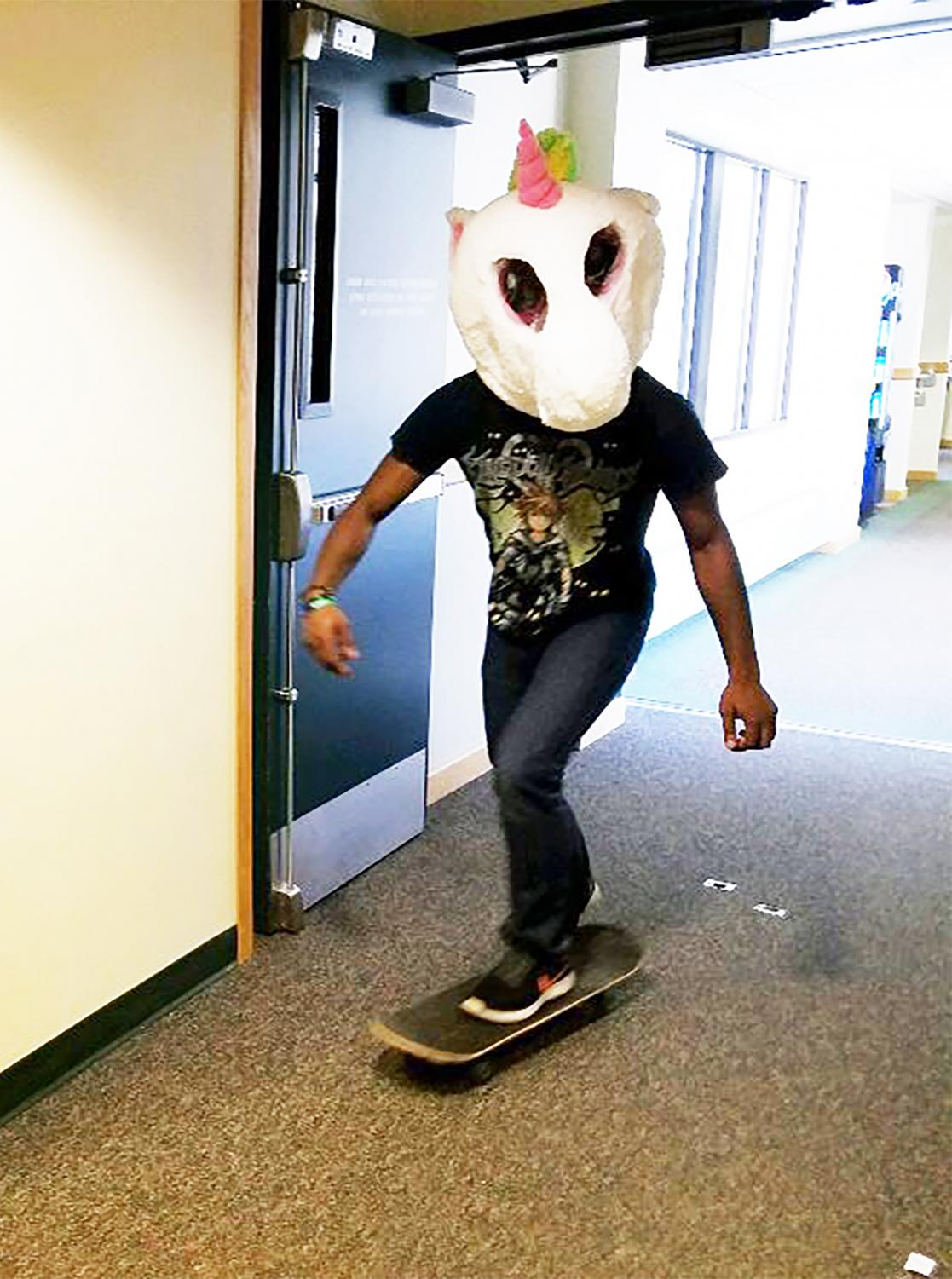Senior Demar Watson rides a skateboard with a unicorn head he won from the Pumpkin Hunt sponsored by Programming Board members.