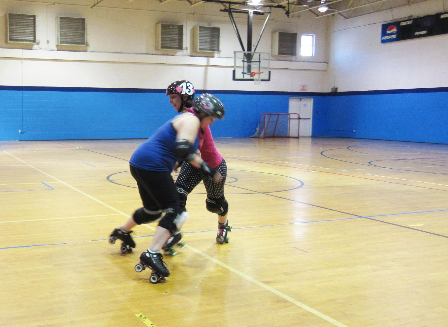 Johnstown Roller Girls team members Barb Mitchell and Kayla Blough, both of Johnstown, demonstrate what it looks like to hit an opponent in a game.