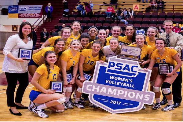 Members of the Pitt-Johnstown volleyball team celebrates with their trophy and plaques after defeating Gannon University in the conference championship Nov. 18 at the Hammermill Center in Erie, Pa.