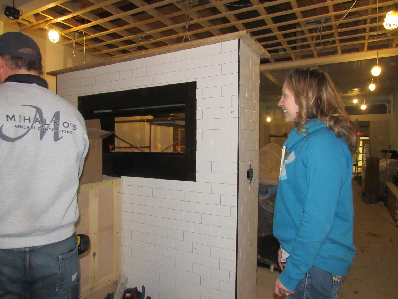 Balance Restaurant owner Amanda Artim shows off a fireplace built between bar and dining areas.