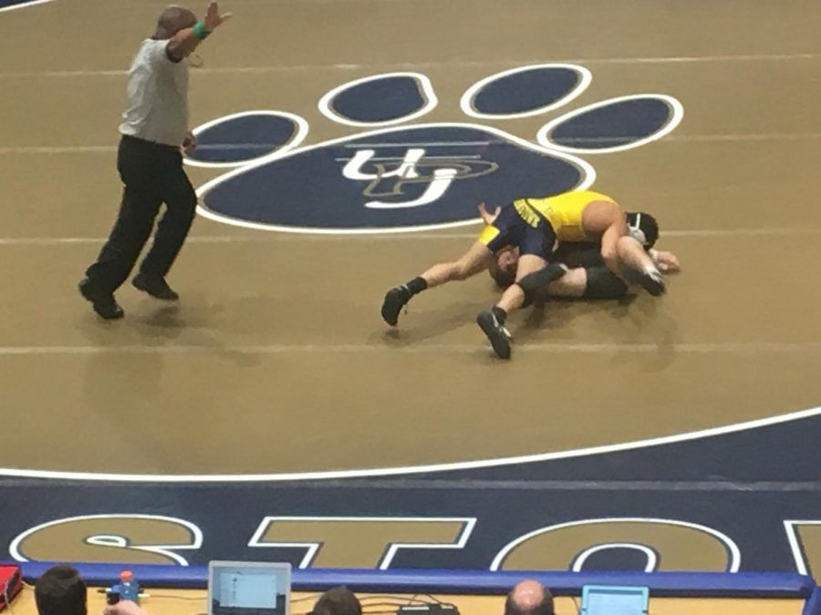 Pitt-Johnstown sophomore wrester Chris Eddins takes down Tyler Warner of Wheeling Jesuit Saturday at the Sports Center. Eddins won his bout 7-0.