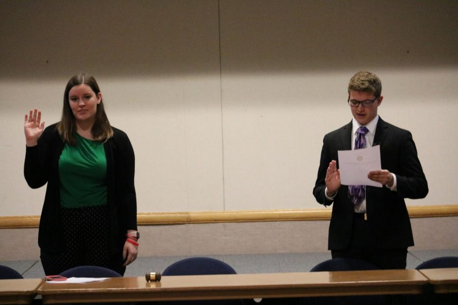 Student government President Sam Miller (right) swears in Vice President Gretchen Shepard (left).