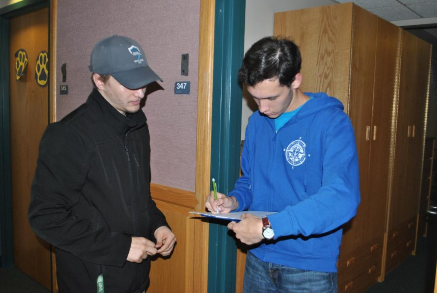 Austin Checco has Living/Learning Center resident Dylan Tuttle sign a petition to lobby for Pitt-Johnstown administrators' attention to living conditions.
