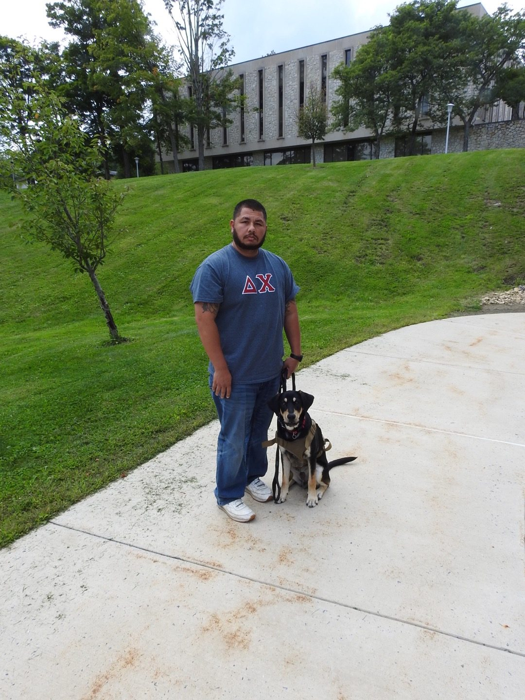 Junior Justin Sprinkle and his service animal, Clyde, standing outside the Nursing and Health Sciences building Aug. 30.