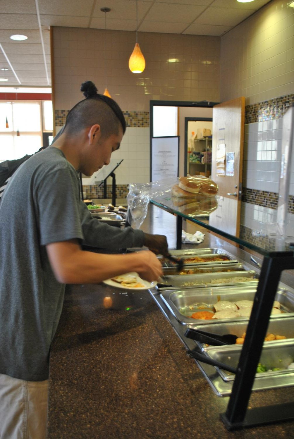 Sophomore Grant Shieh prepares a plate at the Living/Learning Center's Varsity Café, which is soon to be open for dinner hours only.