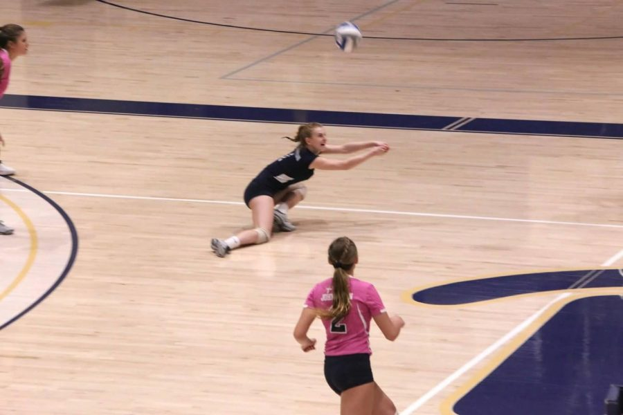 Erin Carmody (in black) saves the ball as teammate J.C. Longeville (toward foreground) watches in a match against Lock Haven in the Sports Center Oct. 12.