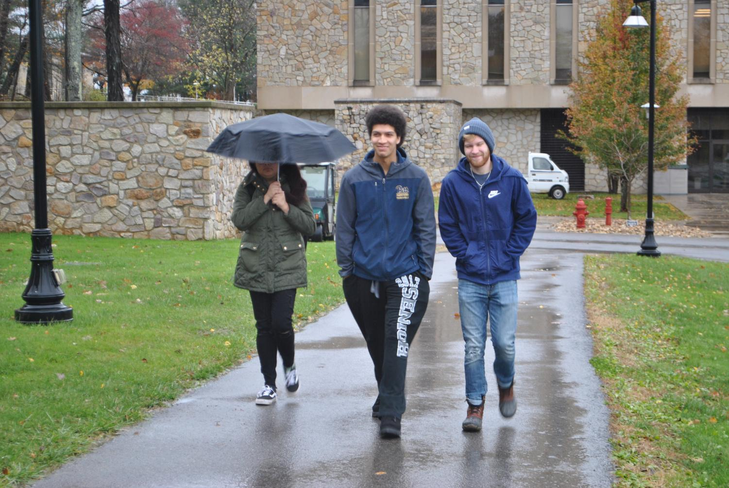 Sophomores Chloe Guerra, Zach Davis and Richard Hartnett brave the cold, wind and rain Friday with fall jackets.