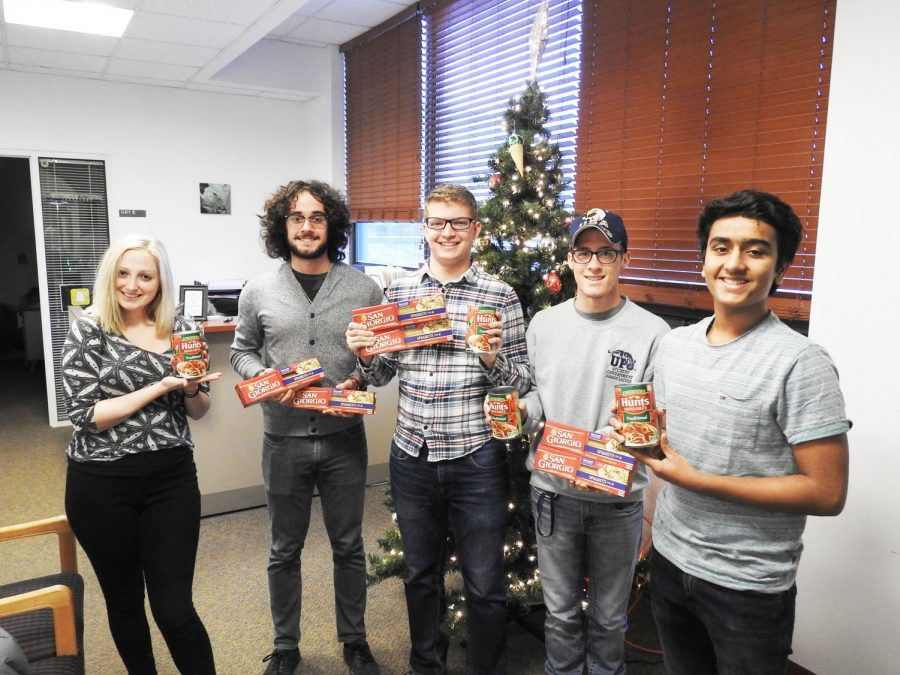 Student government members hold spaghetti noodles and pasta sauce in the Student Union. They are collecting donated goods to assist local families this Christmas. | Photo: Matt Churella