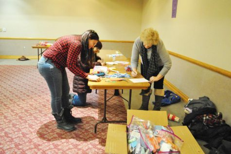 Yamila Audisio, senior (left), Tulsi Shrivastava, senior (center), and Cindy Orlovsky, alumna (right), assemble toiletry bags for The Women's Help Center during the College Democrat meeting Jan. 19, since the trip to the Women's March in New York City was canceled.