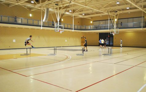 Freshman John Paronish (left) leaps over a hurdle during a track and field team practice at the Wellness Center Jan 23.